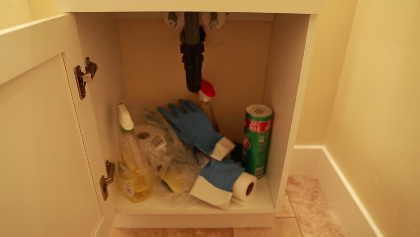 A hand opening a bathroom cupboard to look for cleaning supplies
