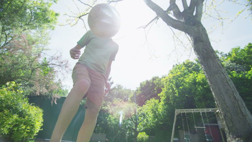 Active young boy practicing his soccer skills in the garden on a bright sunny day. In slow motion.