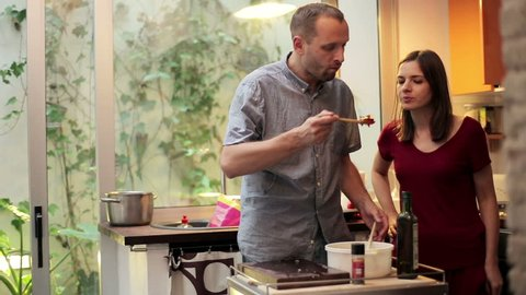 Young couple preparing and tasting a tasteless salad in the kitchen