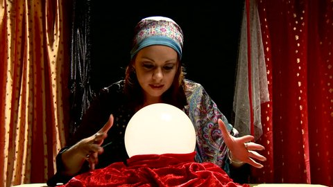 fortune teller gypsy behind crystal ball her fingers move around globe