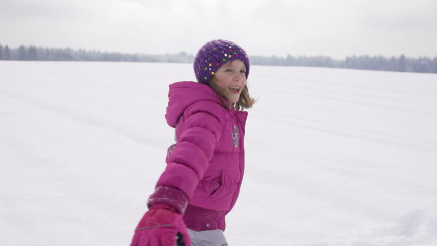 Slow Motion Of A Cute Girl Spinning And Then Throwing Herself In Fresh Snow On A