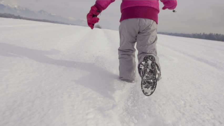 Slow Motion Rear View Of A Girl's Legs Running Across Snow Covered Field On A