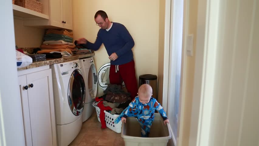 A father does the laundry while his toddler boy plays beside him