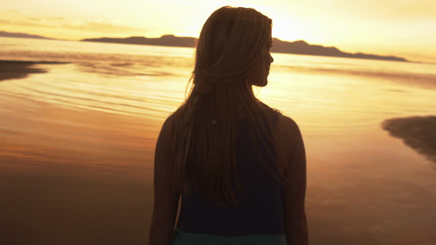 A Teenage Girl On The Beach At Sunset (From Behind)