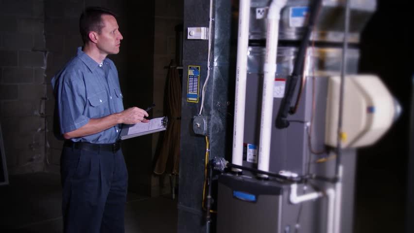 A furnace serviceman inspects a household furnace.