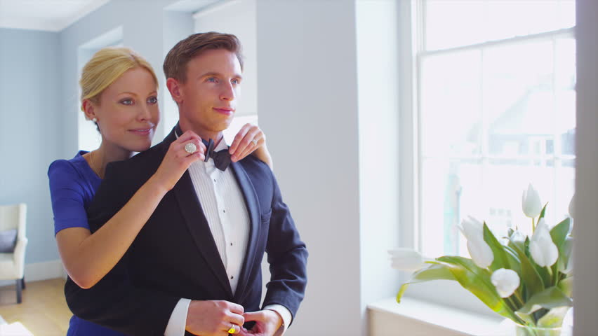 ce6b3f79a163 Attractive young couple in formal evening wear are getting dressed for an  evening out. Young woman adjusts her partner's tie and gives him a kiss.
