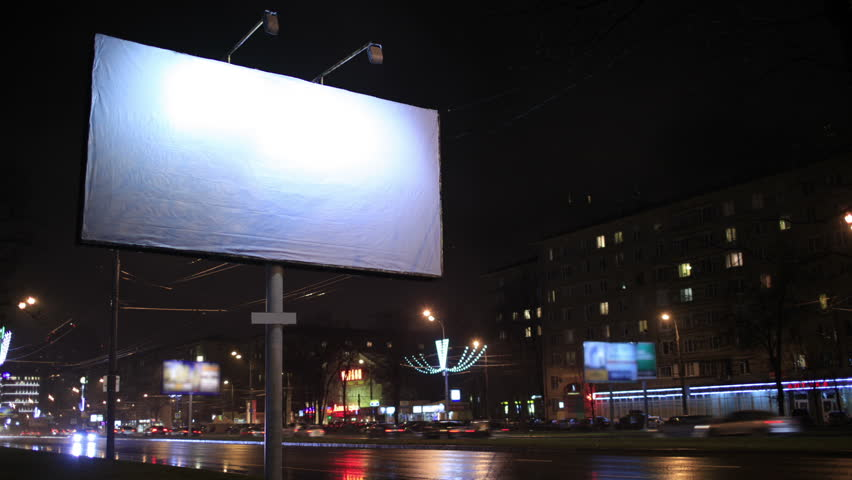 Time lapse of urban scene with an illuminated empty billboard on the side of a street with cars in motion and a block of flats in the background, by night