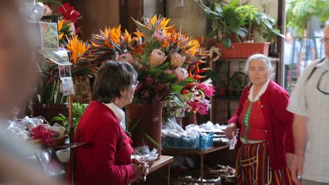 FUNCHAL, MADEIRA/PORTUGAL - NOVEMBER 14: Unidentified women sell flowers on November 14, 2013 in Funchal. The worker's market was built in 1940 to provide a central location to sell local produce.
