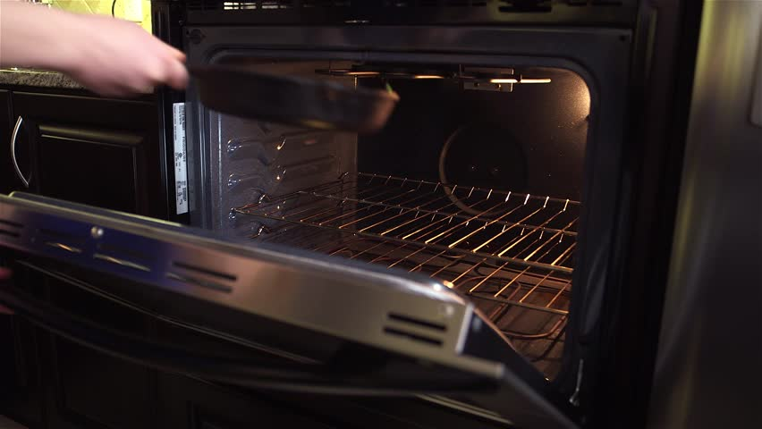 Placing an open faced omelette in a oven.