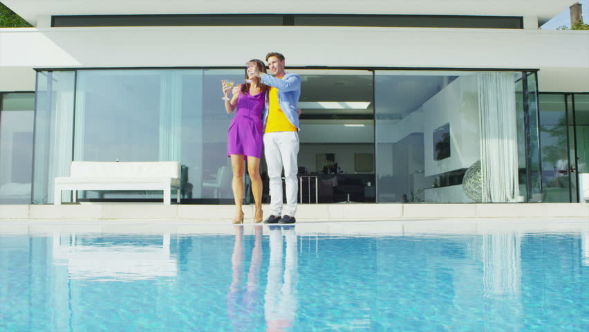 Glamorous young couple enjoying drinks by the pool outside luxury modern home. In slow motion.