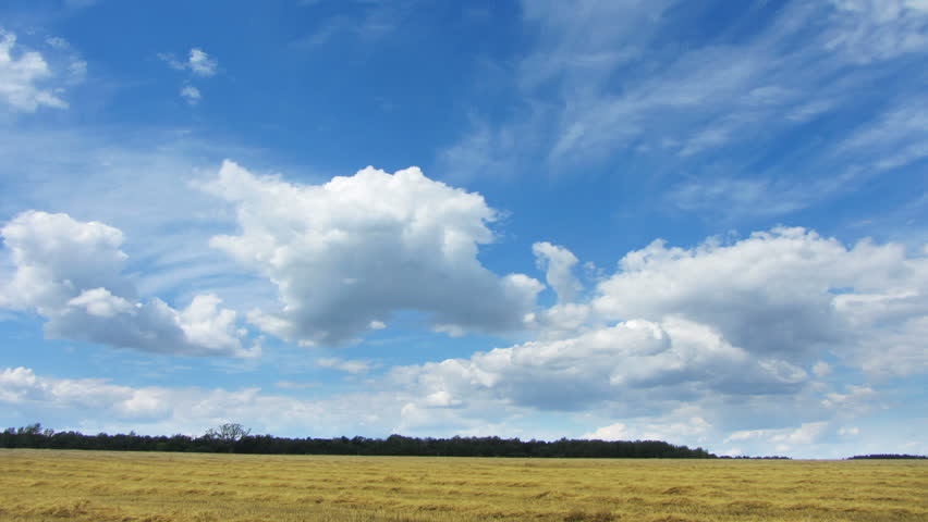 timelapse with clouds moving over yellow field