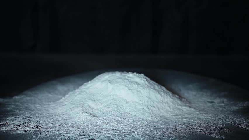 Slow motion video of butter throwing into the heap of flour.