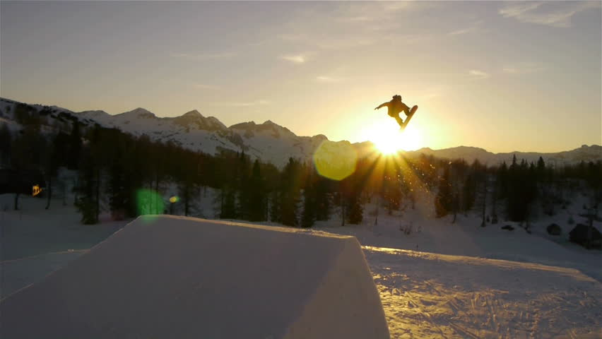 AERIAL: Snowboarder jumping over a kicker in snow park