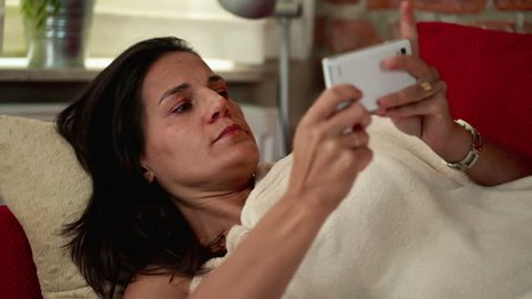 sick woman lying on the sofa and using her cellphone