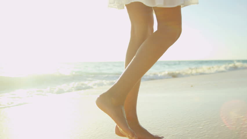 Legs feet Hispanic girl walking barefoot wet sand island beach sun lens flare shot on RED EPIC, 4K, UHD, Ultra HD resolution