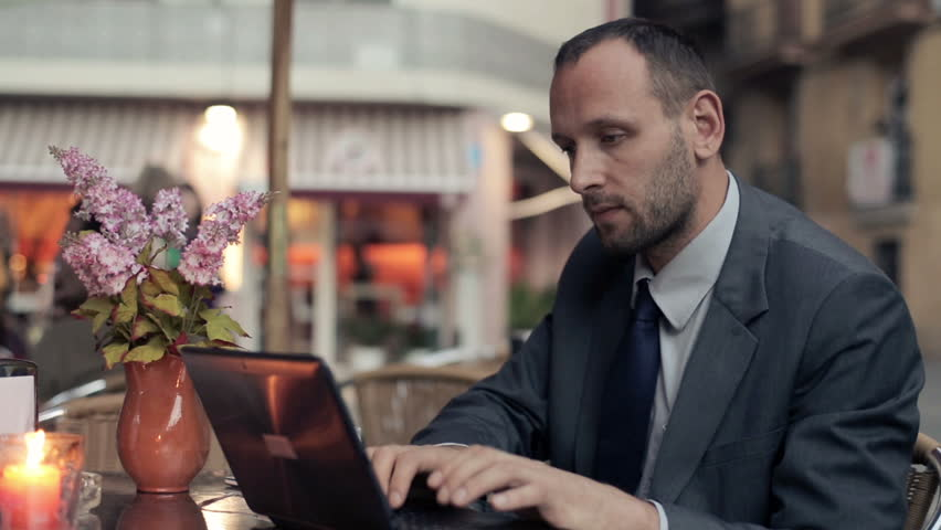 Young businessman working on laptop at the cafe