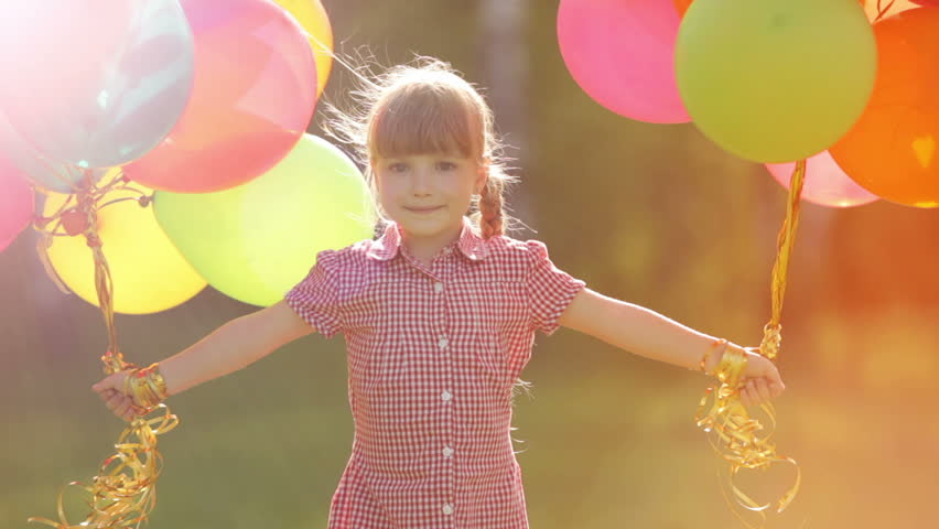 Child spinning with balloons in the park. Girl looking at camera. Lens flare and sunlight | Shutterstock Video #5367914