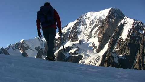 Mountain climber walks on a glacier; in background the beautiful view on Mont Blanc, France - HD1080i