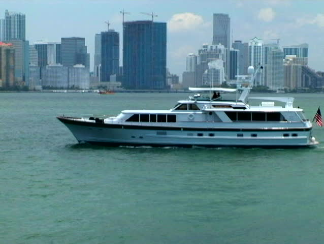 Private yacht crossing in front of the Miami skyline as seen from Biscayne Bay bridge