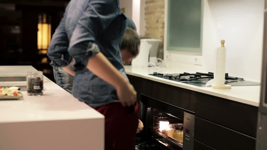 Man taking food from oven in the kitchen
