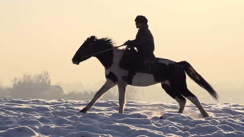 Horseman. A man on a horse galloping on a snowy field on a background of foggy sky illuminated by the sun. Slow Motion at a rate of 240 fps
