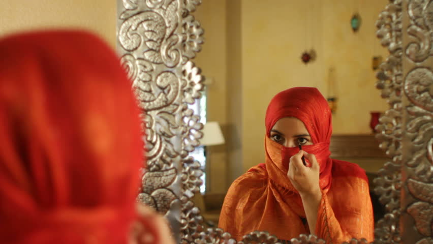 Arabic Woman In Orange Hajib Applies Eyeliner