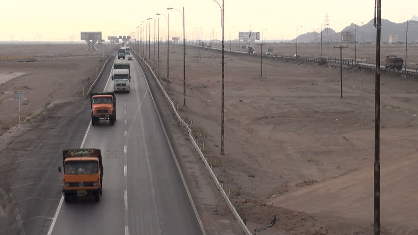 YAZD, IRAN - 5 NOVEMBER 2013: Trucks and other traffic drive across the major highway connecting Bandar Abbas along the Persian Gulf with Tehran, capital of Iran