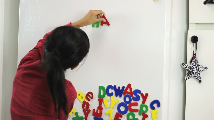 A cute little seven year old Asian girl uses colorful fridge magnet letters to spell Happy Birthday!