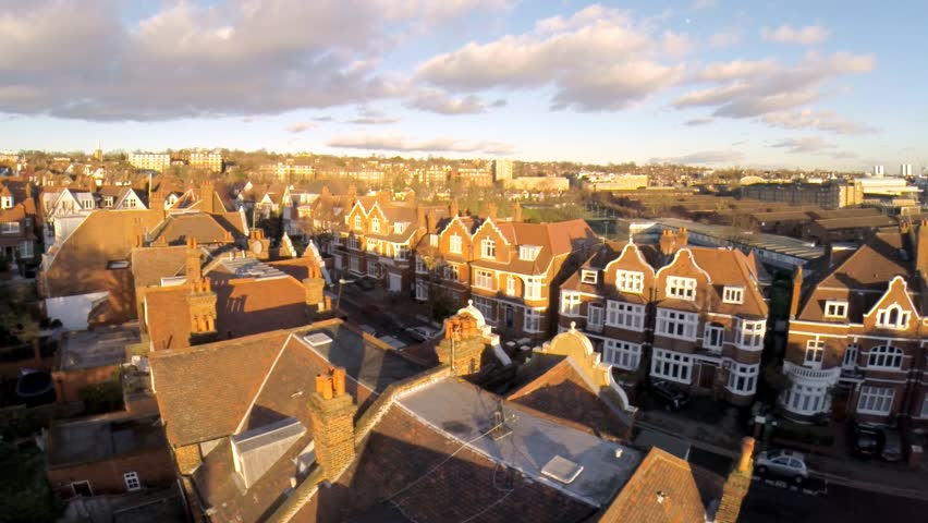 Flying above London surburban houses and apartments aerial view at dawn on sunny day
