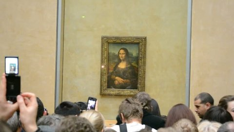"PARIS - JAN 02: Visitors take photos of Leonardo DaVinci's ""Mona Lisa"" at the Louvre Museum on January 02, 2014 in Paris, France. The painting is one of the world's most famous works of art."
