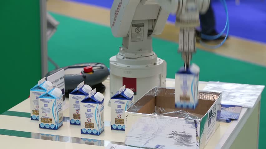 MOSCOW, RUSSIA - OCT 11, 2012: Robot packs milk at AgroProdMash - International Trade Fair for Machinery, Equipment and Ingredients for Food Processing Industry in Expocentre.