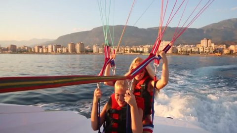 Happy woman and boy fly on glider over sea at sunny summer evening