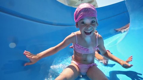 two girls and boy rolls on blue waterslide and smiles