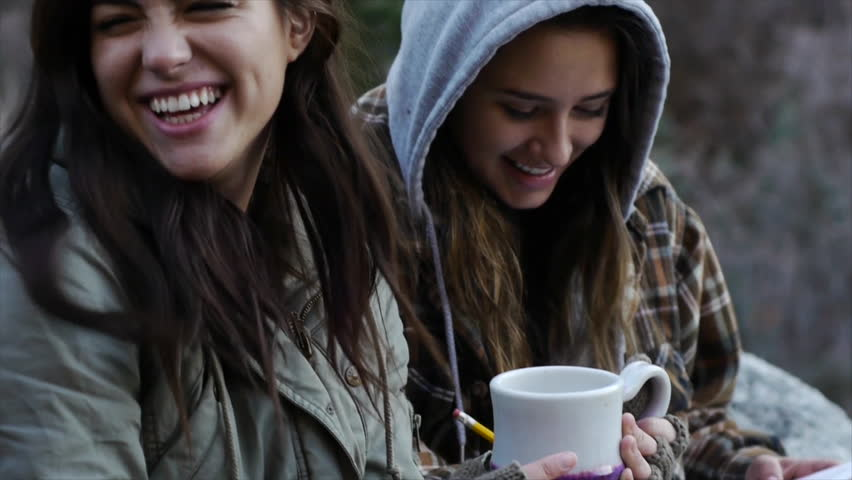 Two Teen Girls Bundled Up Outdoors, Enjoying Something On Paper