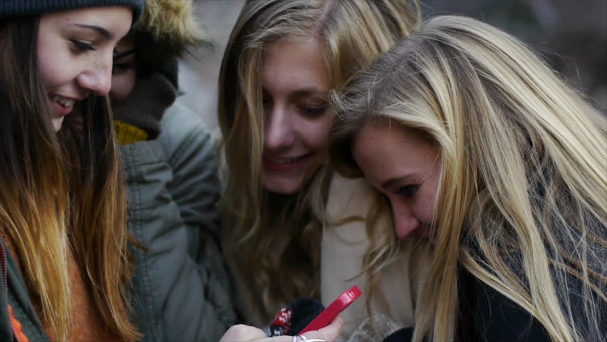 Group Of Bundled-Up Teen Girls Laughing At A Smart Phone in slow motion