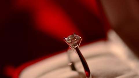 Diamond ring. Valentine's Day Gift. Marriage Proposal. Beautiful Ring - white gold with big diamond (one carat) on red silk background. Rotation