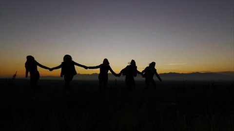 Silhouettes Of 5 Teen Girls Holding Hands Turn, Run Toward & Past Camera At Dusk