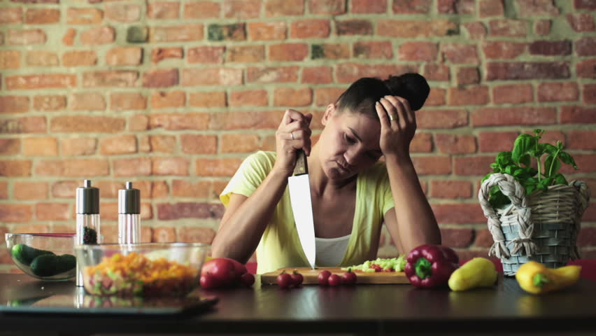 Bored woman preparing vegetable salad