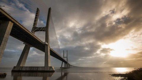 Time Lapse of Vasco da Gama Bridge over the Tagus river at sunrise with cloudy sky. Lisbon, Portugal.