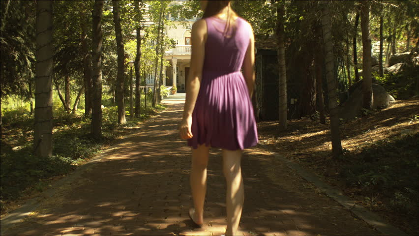 Beautiful teen girl walks down tree-lined lane toward a large white manor home