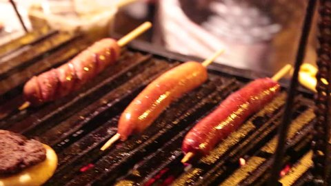 Hot Dogs, Burgers, and Sausages Cooking and Basted on a Grill