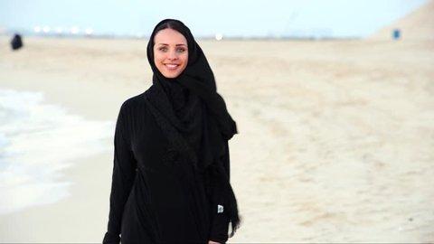 Middle eastern woman. pretty lady walks at sunset alone sea coast.