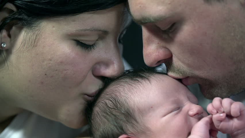 Both parents kiss baby boy's head at the same time
