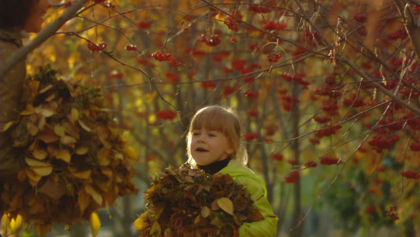 Sequence of slow motion shots happy mum and the little girl throw autumn leaves.