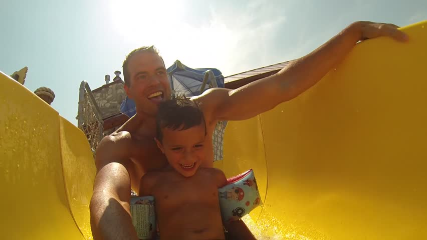 Attractive athletic and healthy father going down a bright colored water slide with his young son and a clear beautiful Summer afternoon.