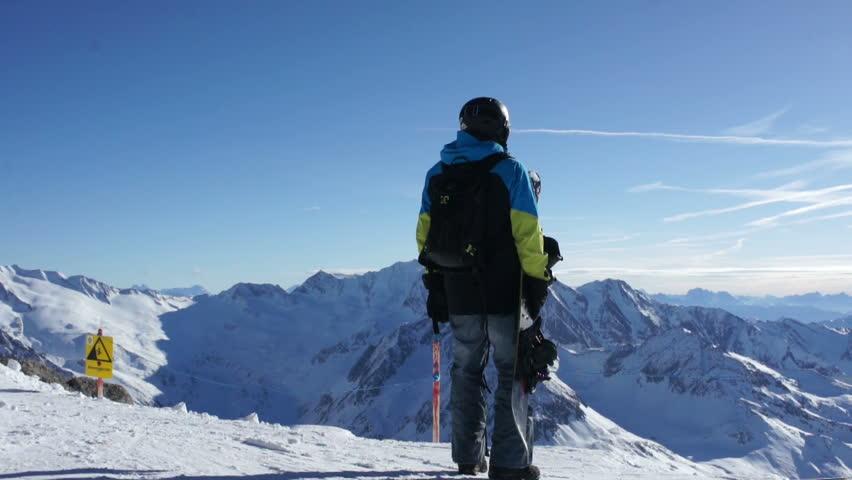 Man with snowboard standing on top of snowy mountain, Hintertux glacier, Tirol, Austria