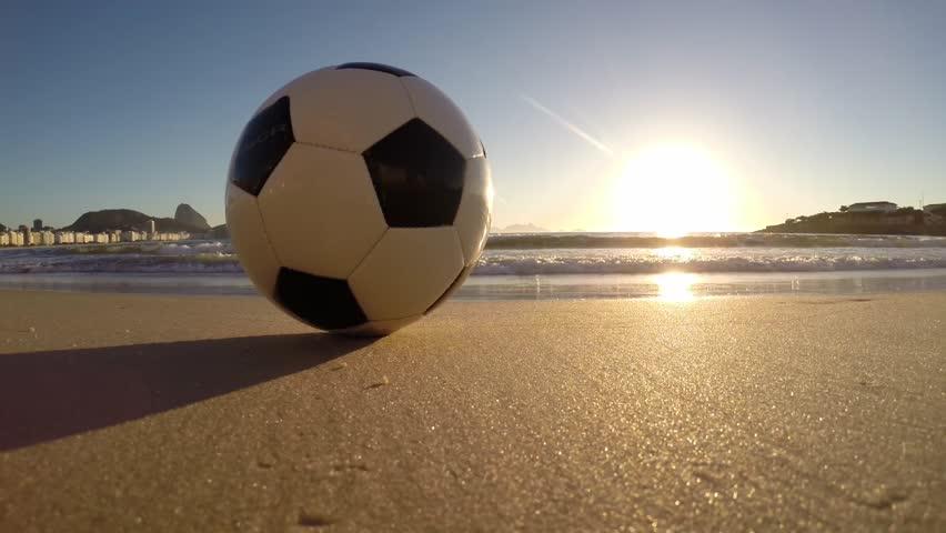Rio de Janeiro Brazil soccer football golden sunrise with lapping waves on Copacabana Beach