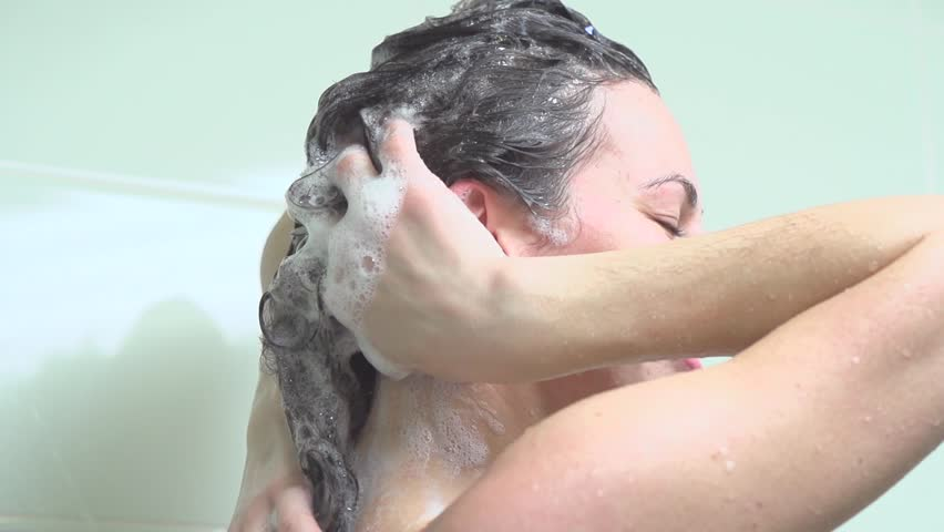 Shower. Young woman taking a shower and washing hair with shampoo. Beautiful girl enjoying a shower. Body care. Slow motion video footage 240fps. Foam and Bath. Douche