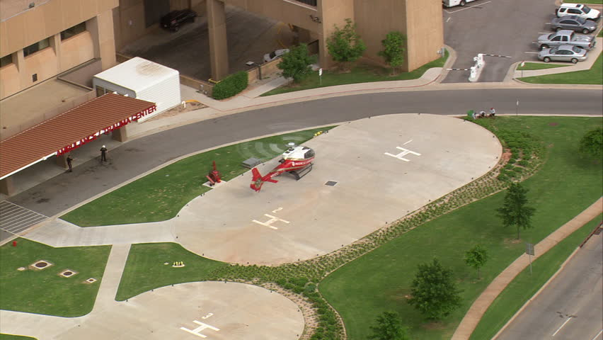 Helicopters in grounds of hospital building - Pull back to reveal City Hospital, Oklahoma