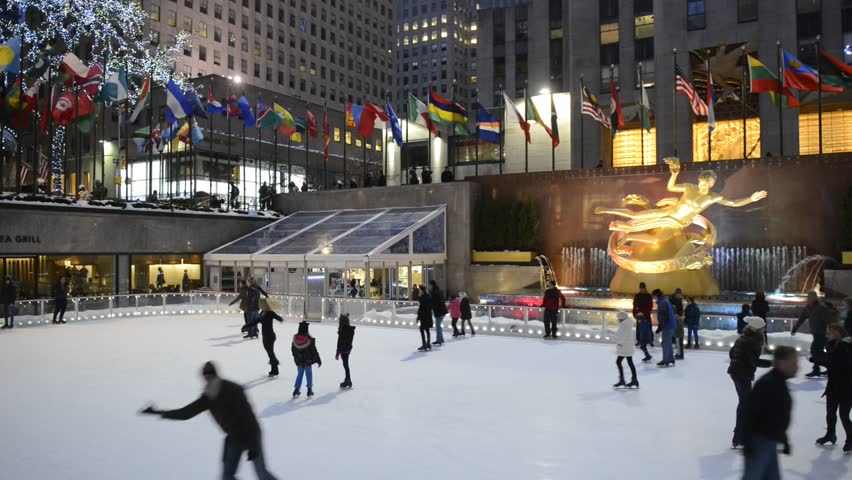 NYC – FEBRUARY 9, 2014: Visitors to the Rockefeller Center skate around in the ice skating rink at night
